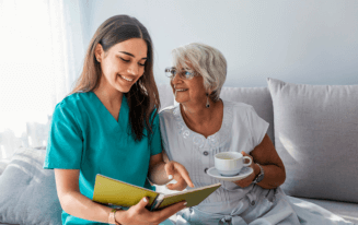 caregiver helping patient holding coffee to read