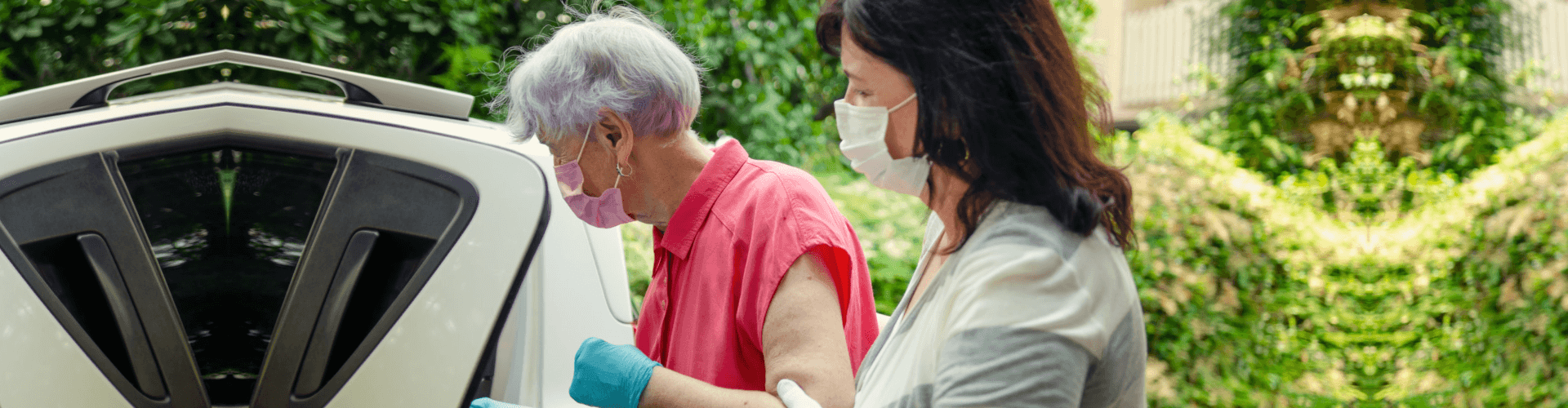 caregiver helping patient going inside a car